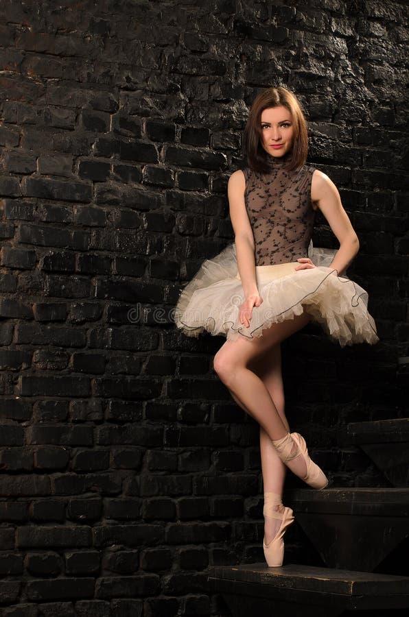 芭蕾舞女演员在楼梯站立在砖墙附近 免版税库存图片