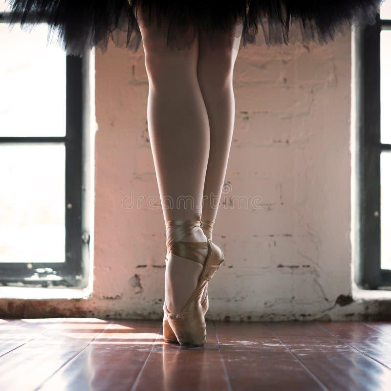 芭蕾舞女演员特写镜头的腿 一位芭蕾舞女演员的腿老pointe的 排练芭蕾舞女演员在大厅里 从窗口的等高光 免版税库存照片