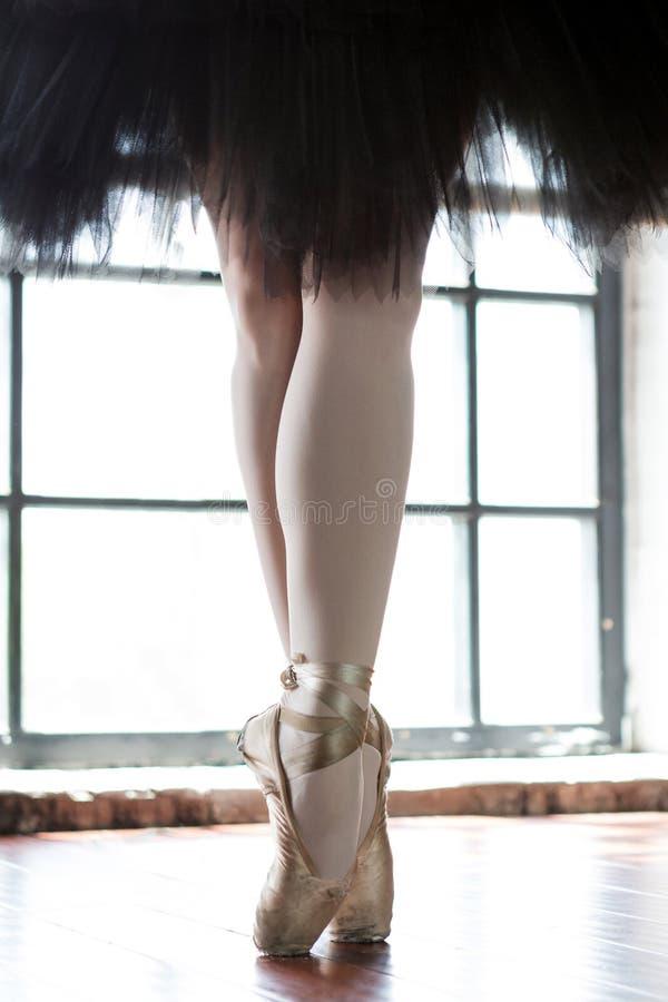 芭蕾舞女演员特写镜头的腿 一位芭蕾舞女演员的腿老pointe的 排练芭蕾舞女演员在大厅里 从窗口的等高光 库存照片