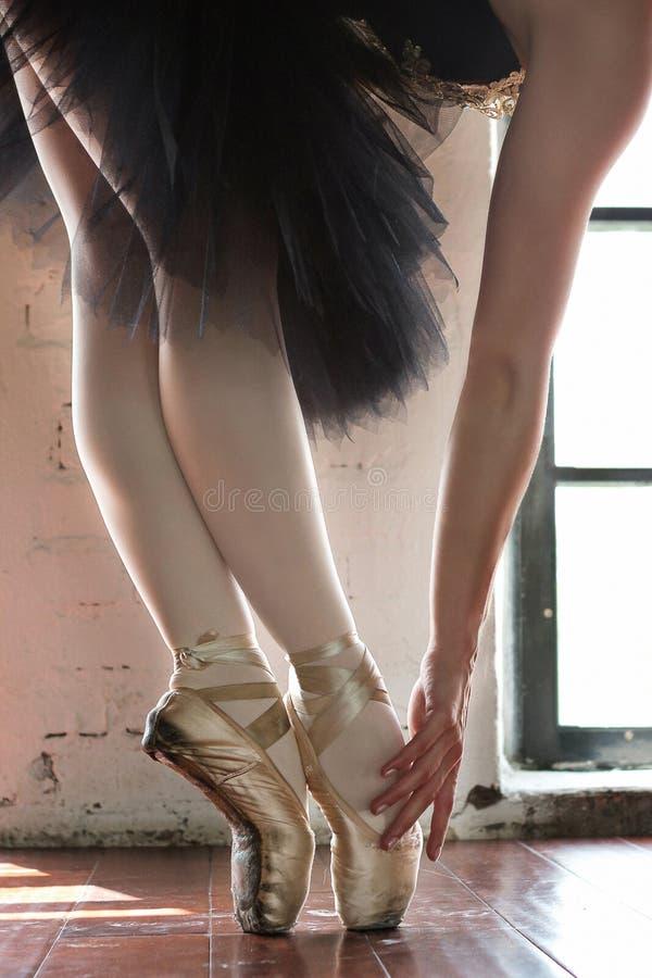 芭蕾舞女演员特写镜头的腿 一位芭蕾舞女演员的腿老pointe的 排练芭蕾舞女演员在大厅里 从窗口的等高光 免版税库存图片