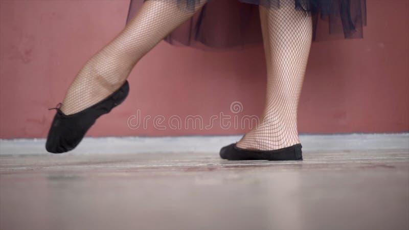芭蕾舞女演员的腿特写镜头在黑pointe鞋子的 r 黑捷克人和滤网贴身衬衣的芭蕾舞女演员揉她的腿 免版税图库摄影