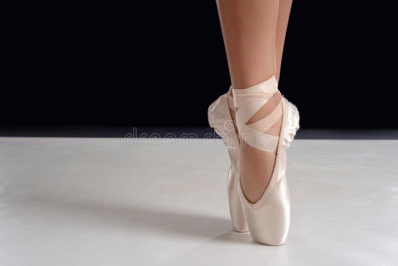 芭蕾舞女演员脚特写镜头在pointe的在pointe鞋子 免版税库存图片