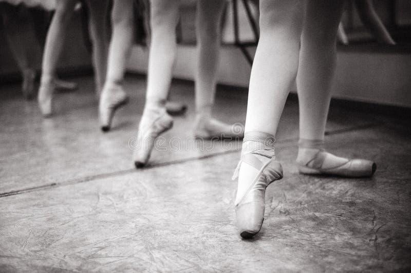 芭蕾舞女演员脚特写镜头在pointe鞋子的在舞厅里 v 图库摄影