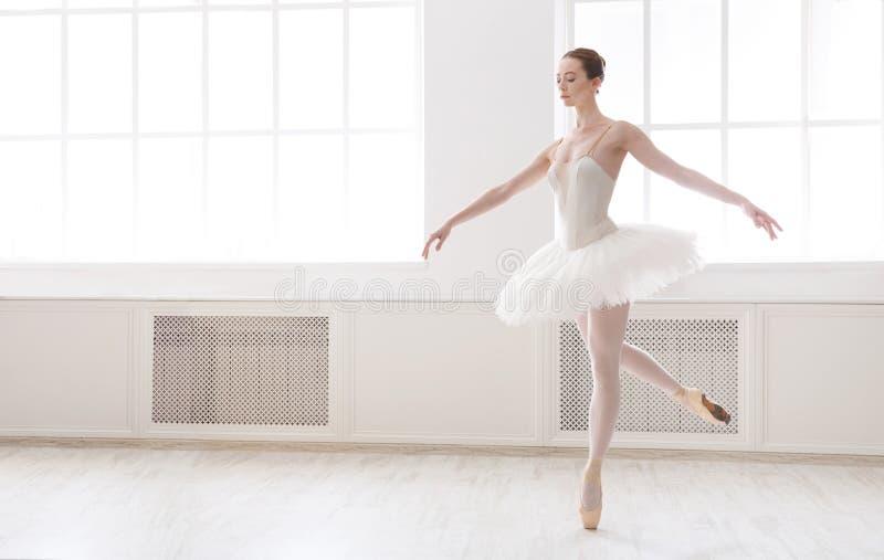芭蕾舞短裙裙子的美丽的芭蕾舞女演员在大窗口附近 免版税库存照片