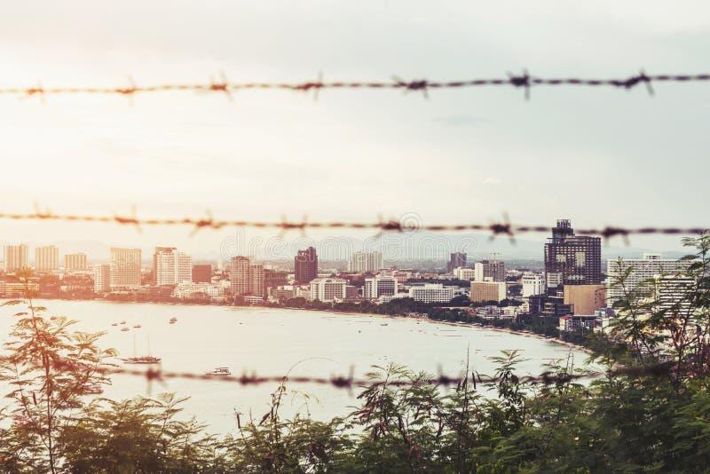 芭达亚市和岸城市空间在日出,与被弄脏的铁丝网前景,抽象概念,葡萄酒口气 免版税库存照片