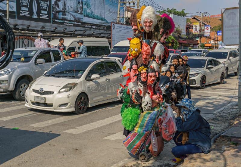 芭达亚,泰国- 4月18,2018:北部芭达亚路A泰国妇女为Songkran卖面具和水枪 免版税图库摄影