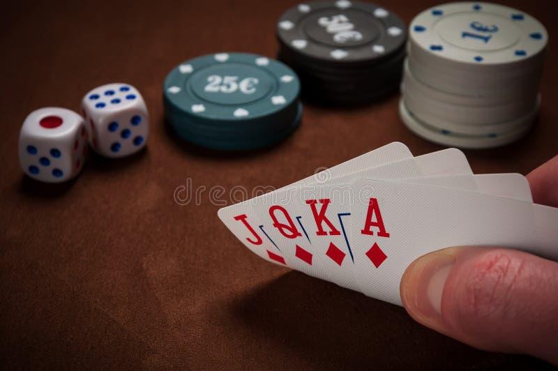 芯片和卡片啤牌的在手中在桌上 库存图片