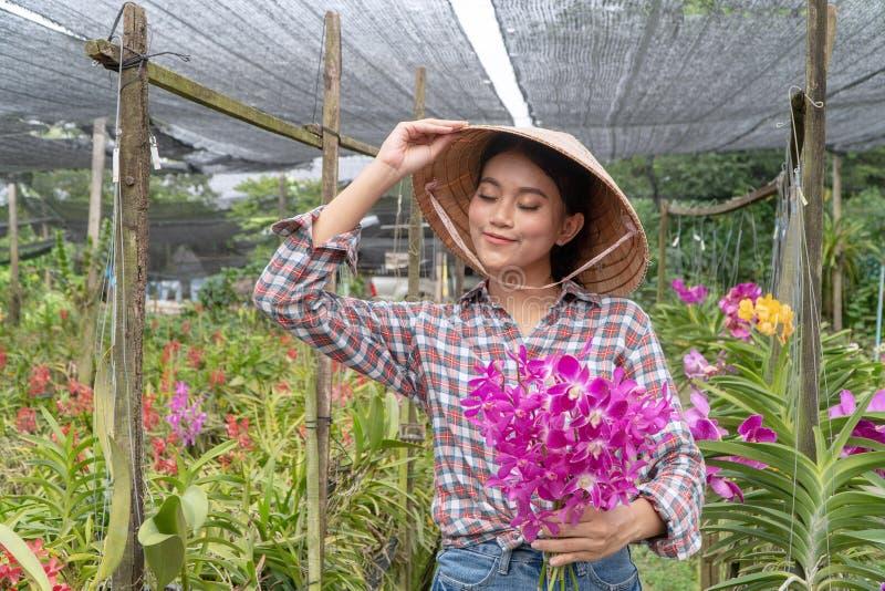 花匠安排拿着帽子的兰花庭院 并且拿着兰花在兰花庭院里 图库摄影