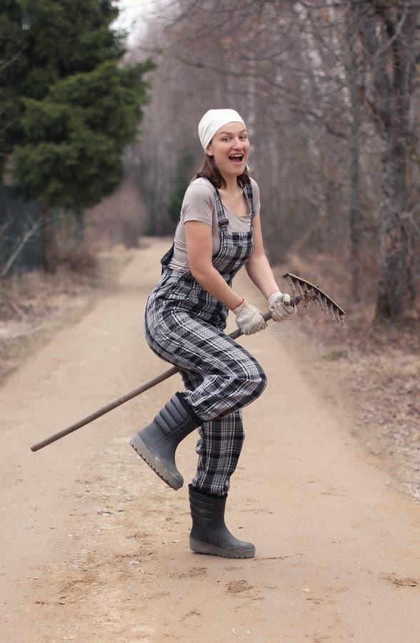 花匠或农夫妇女骑马犁耙,象在棍子马 autum 库存照片