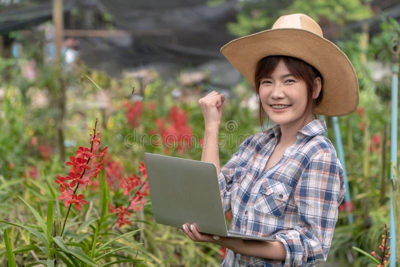 花匠通过拿着笔记本和拿着右手安排了兰花庭院 表达喜悦和增量销售 免版税库存照片