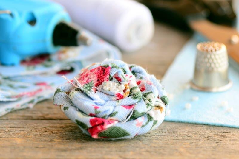 花卉亚麻制别针 织品用小珠装饰的花别针,热的胶水枪,剪刀,螺纹短管轴,顶针,毛毡板料 免版税库存照片