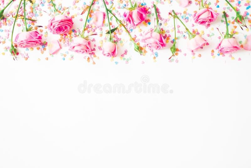 花卉框架由桃红色花和明亮的糖果五彩纸屑制成在白色背景 平的位置,顶视图 玫瑰花纹理 免版税库存图片