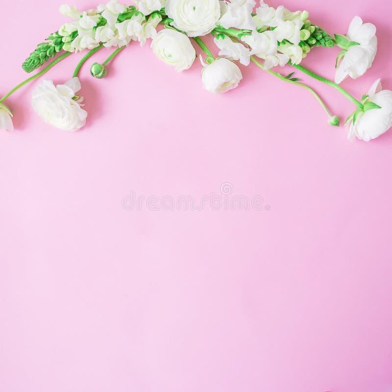 花卉框架由白花制成在柔和的桃红色背景 平的位置,顶视图 花束弓形象花纹花样无缝小 免版税库存图片