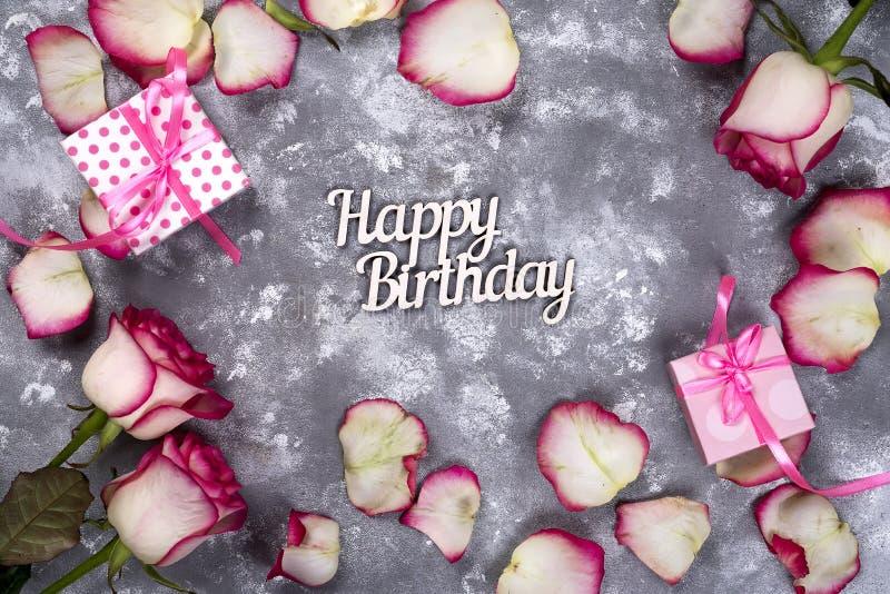 花卉框架:桃红色白玫瑰和在石背景的信件生日快乐花束与礼物盒的 免版税库存图片