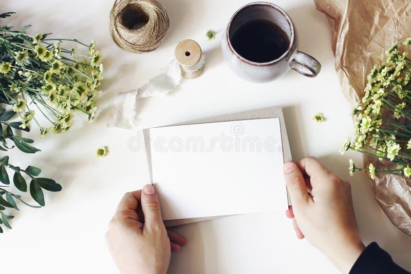 花卉生活方式构成 与妈咪花、绿叶和咖啡的大模型场面在白色桌上的 女性手 图库摄影