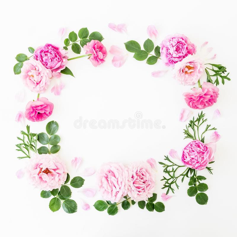 花卉花圈框架由桃红色玫瑰和牡丹做成与绿色叶子在白色背景 平的位置,顶视图 背景花光playnig 免版税图库摄影