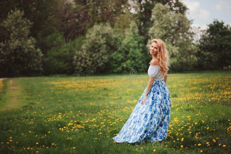 花卉蓝色最大的裙子的美丽的少妇走在春天的 免版税库存照片