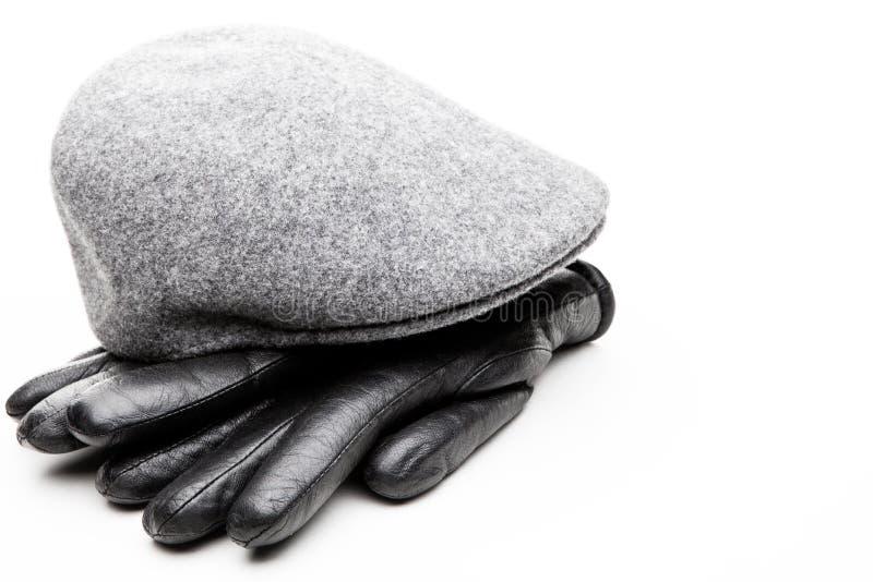 花呢灰色盖帽黑色皮手套白色背景 免版税库存照片
