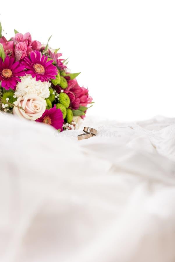 花和两个婚戒美丽的五颜六色的花束在w 库存照片
