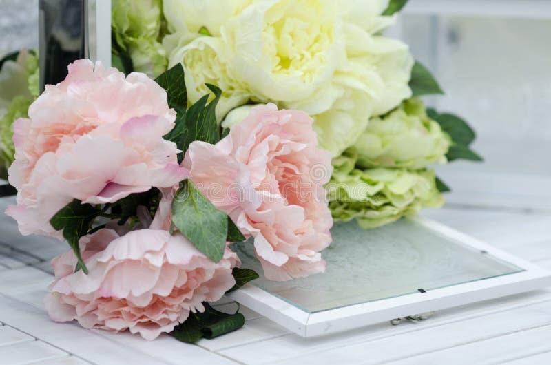花和灯在白色木桌上 免版税库存照片