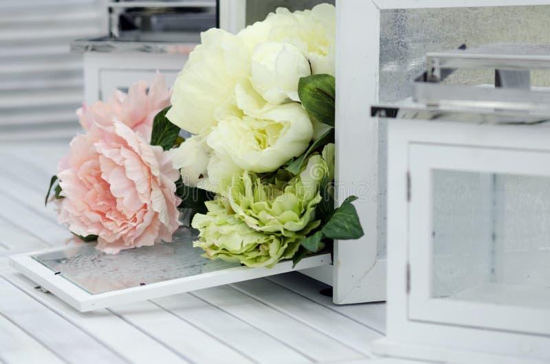 花和灯在白色木桌上 免版税图库摄影