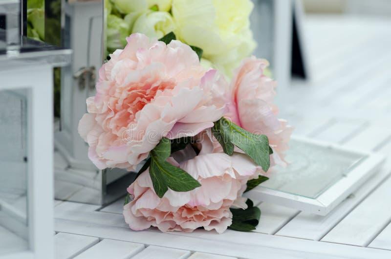 花和灯在白色木桌上 图库摄影