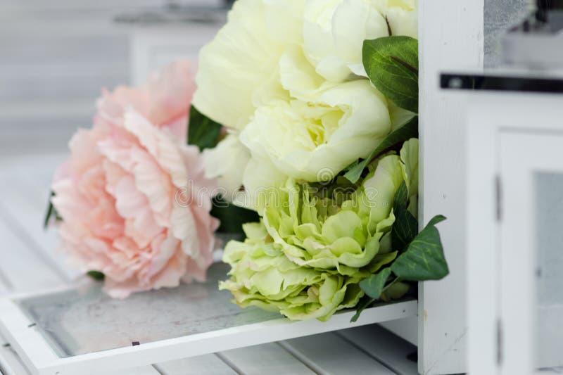 花和灯在白色木桌上 库存照片