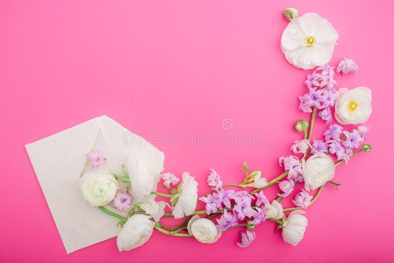 花和纸信封在桃红色背景 平的位置,顶视图 来回花卉的框架 免版税库存图片