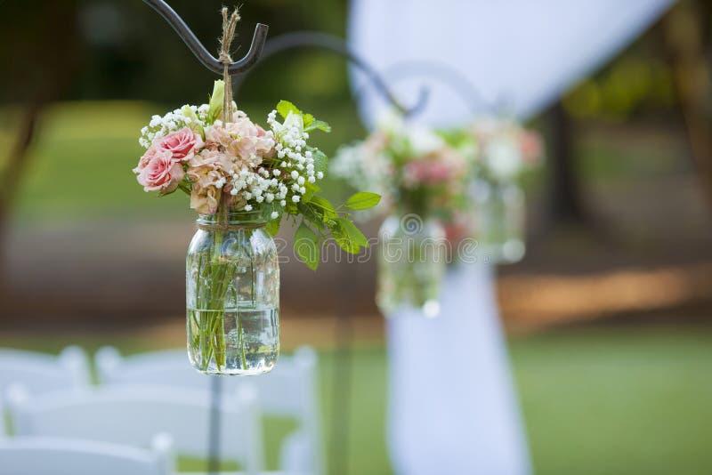 花和金属螺盖玻璃瓶在婚礼 库存照片
