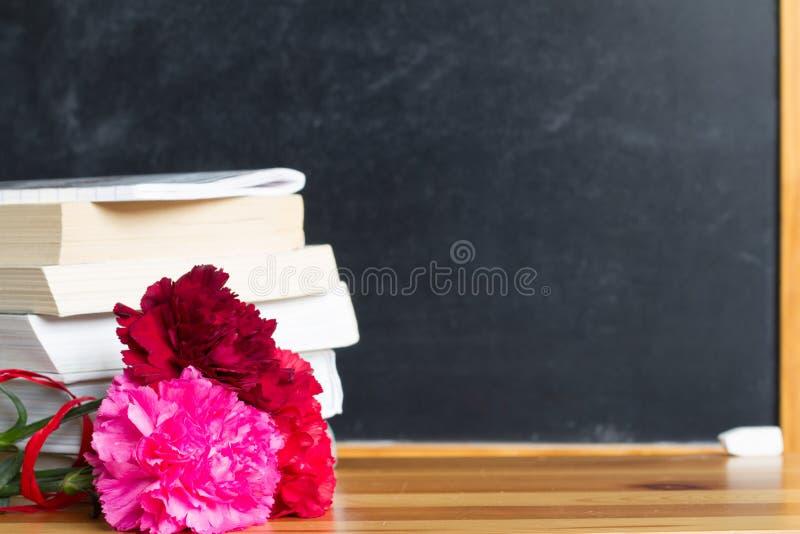 花和黑板在教室老师天背景概念 免版税库存照片