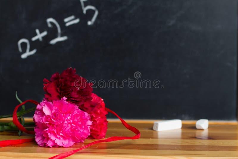 花和黑板在教室老师天背景概念 免版税图库摄影