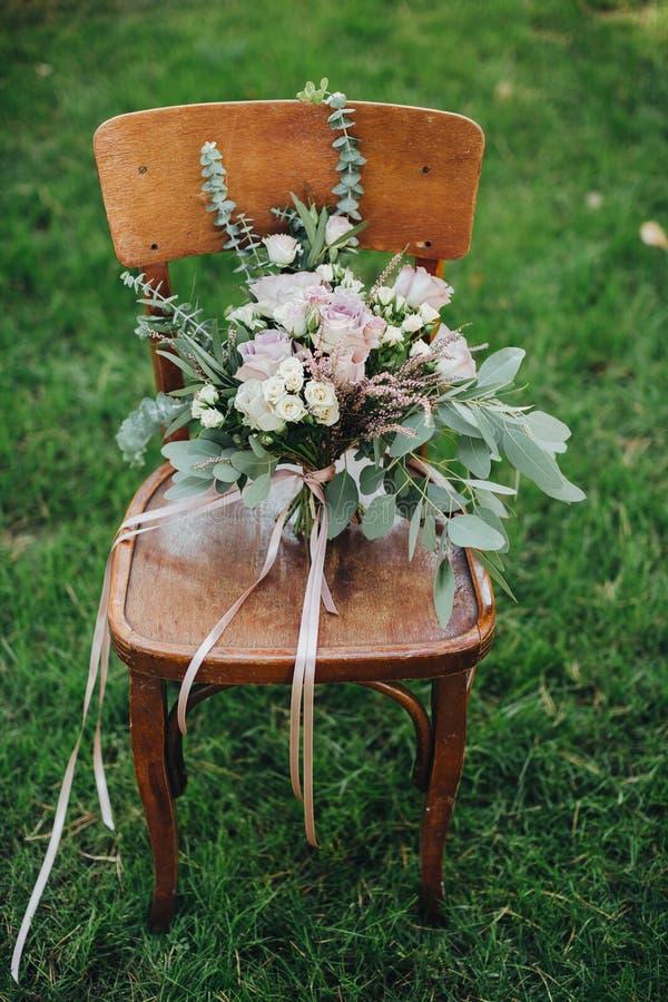 花和绿叶婚礼花束在绿草的一把木椅子站立在森林里 免版税图库摄影