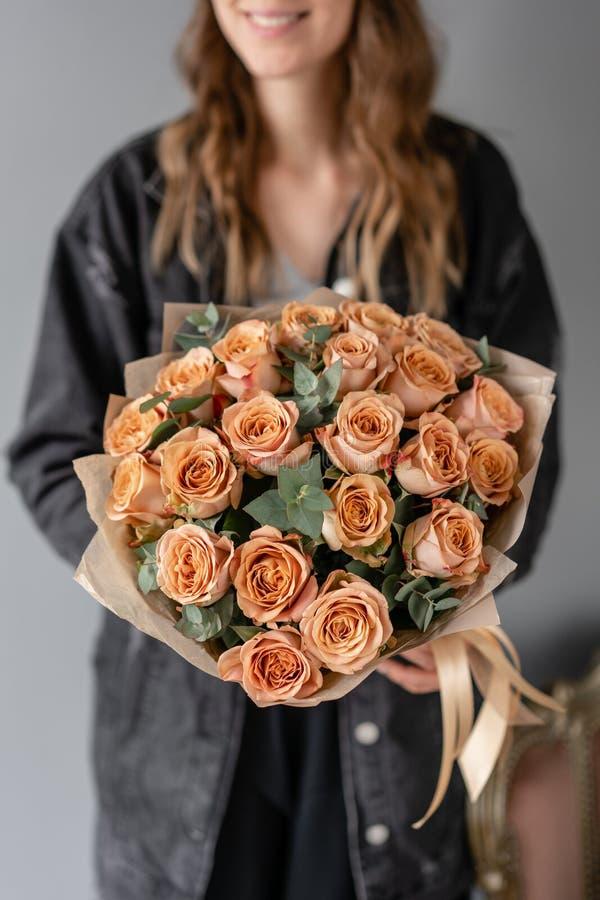 花咖啡颜色,与玉树的热奶咖啡玫瑰 小美丽的花束在妇女手上 花卉商店概念 免版税库存照片