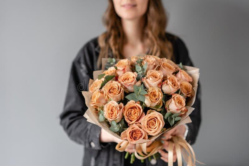 花咖啡颜色,与玉树的热奶咖啡玫瑰 小美丽的花束在妇女手上 花卉商店概念 免版税库存图片