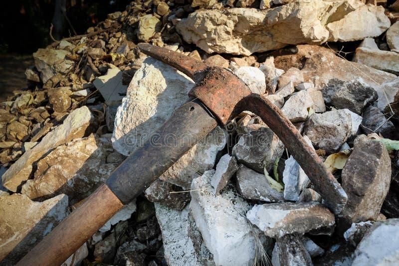 花园里堆石头上的老锈斧 库存照片