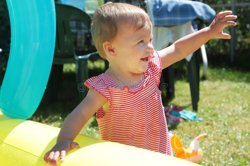花园里,一个穿条纹衬衫的可爱女孩站着 免版税图库摄影