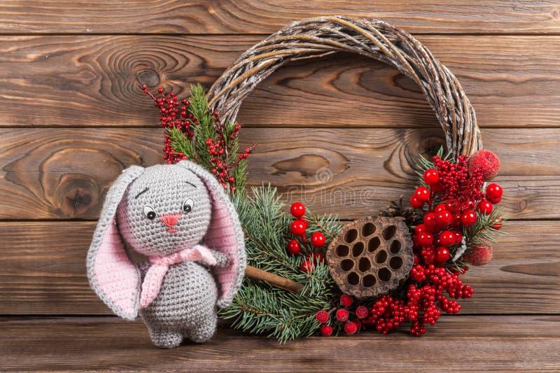 花圈和野兔兔子 圣诞节在黑暗的木背景的冬天框架 红色元素钩编编织物卡拉服特玩具 免版税库存图片