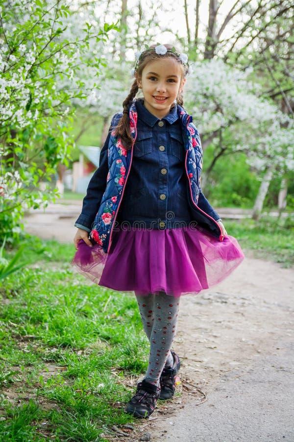 花圈的女孩享用春天庭院的 库存照片