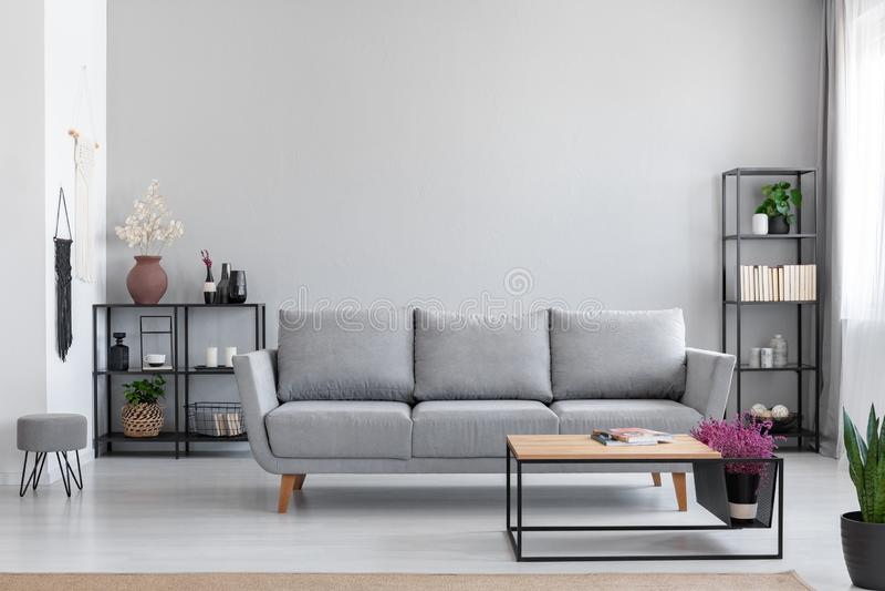 花在灰色长椅前面的木桌里在现代简单的公寓内部与凳子 图库摄影