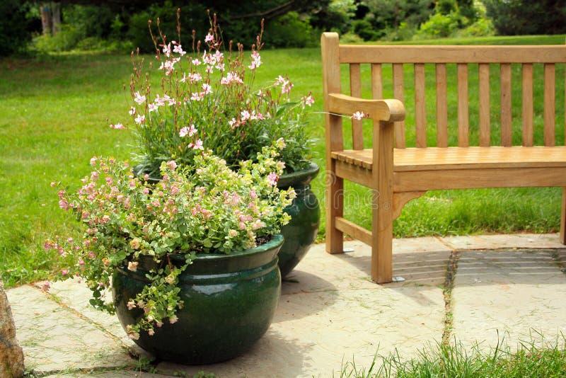 花在长木凳旁边的庭院里 库存照片