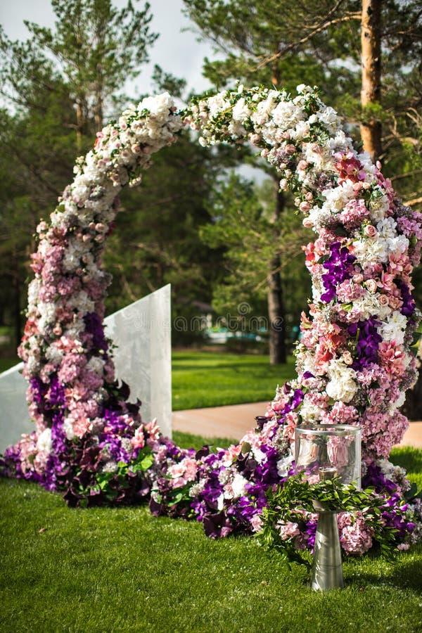 花婚礼曲拱与火炬的在室外仪式 免版税库存照片