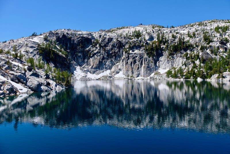 花岗岩岩石和反射在镇静水中 免版税库存图片