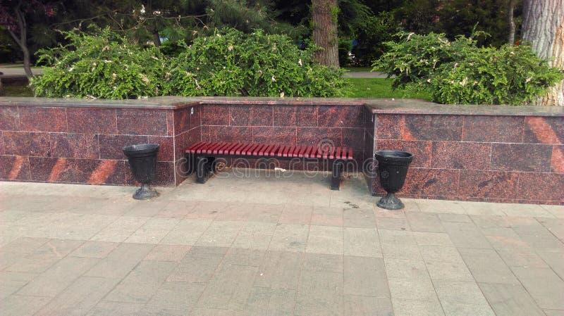 花岗岩平板围拢的美丽的长凳在公园 免版税图库摄影