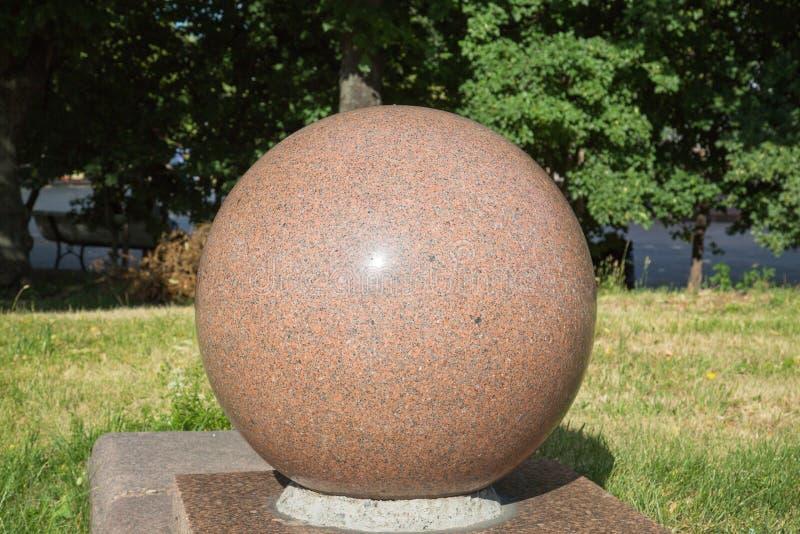 花岗岩球的看法浅褐色在一个垫座在公园 库存图片