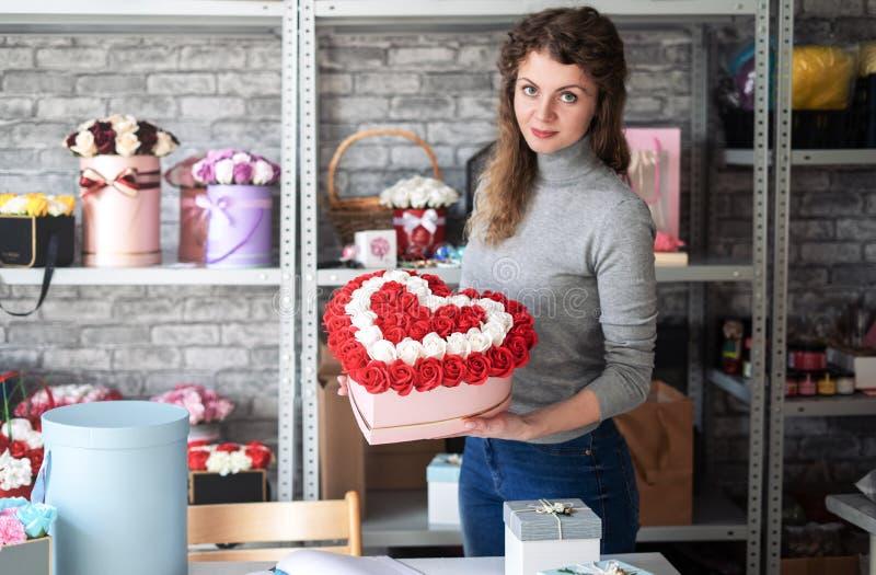 花店:卖花人女孩展示在车间集合的红色和白玫瑰大心形的花束  免版税库存图片
