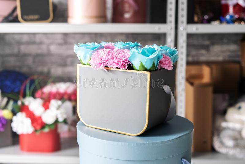 花店:蓝色玫瑰和桃红色康乃馨小花束在一个灰色箱子 免版税库存图片