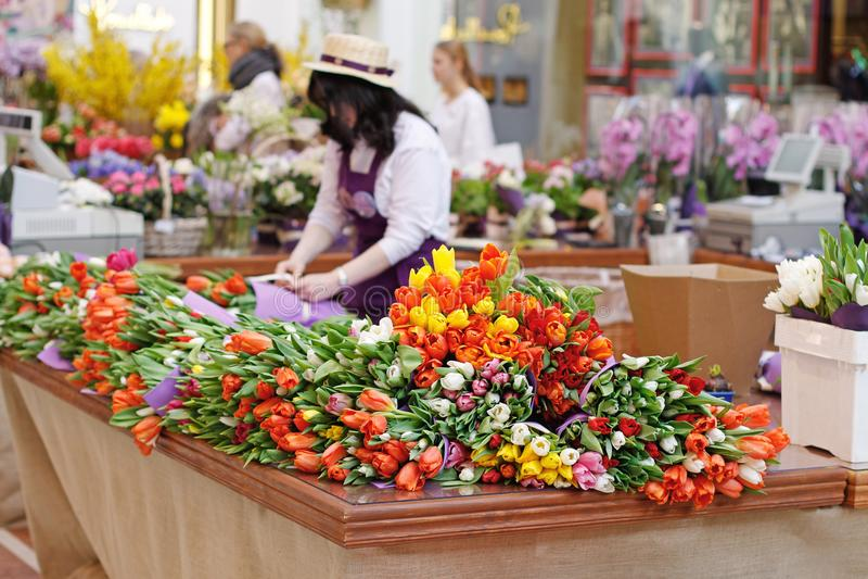 花推销员郁金香花束为在购物中心` Petrovsky段落`的销售做准备在花的莫斯科焦点 免版税库存图片