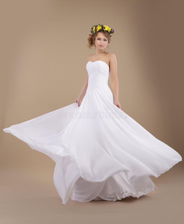 花春天花圈的妇女在飞行婚礼礼服的 免版税库存照片