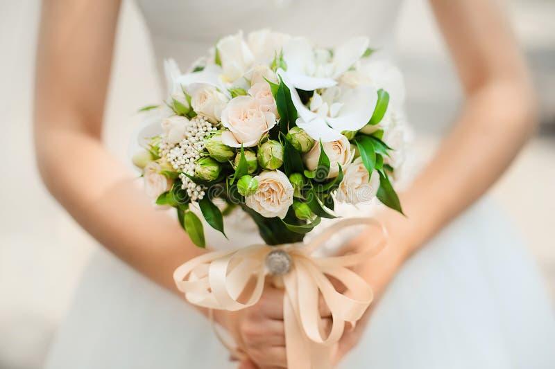 花束在从灌木玫瑰的新娘的手上 免版税库存图片