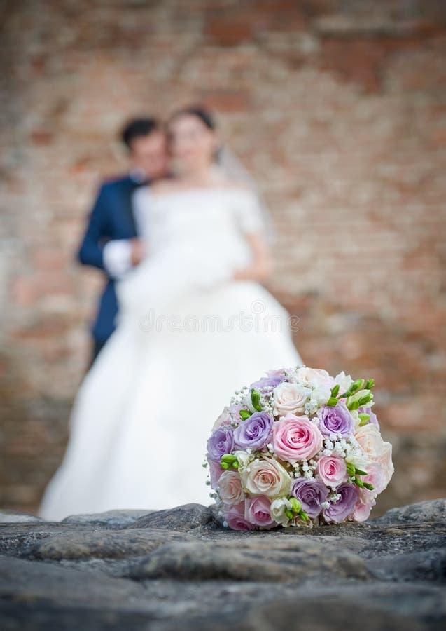 花束夫妇前景最近与婚姻黄色的玫瑰结婚 与婚礼夫妇的婚礼花束在背景中 图库摄影